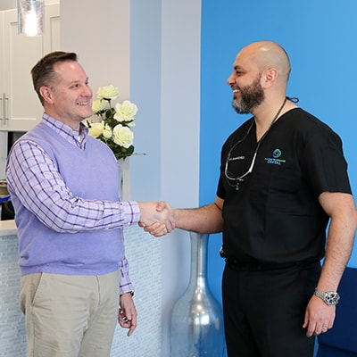 Dr. Yadani shaking hands with a patient in his Manchester dental office